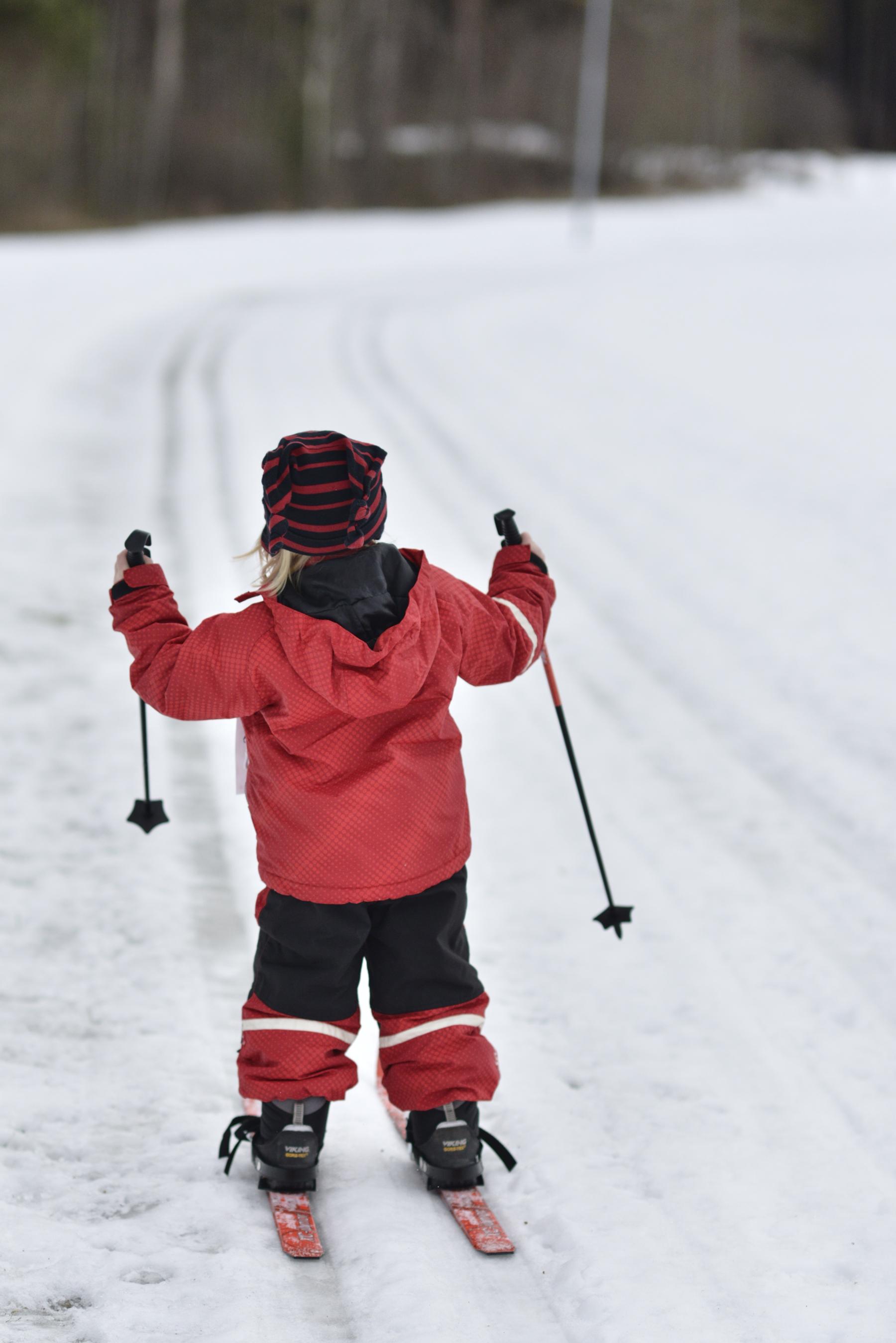 pieni tyttö hiihtää