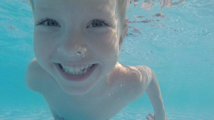 Poika sukeltaa uima-altaassa