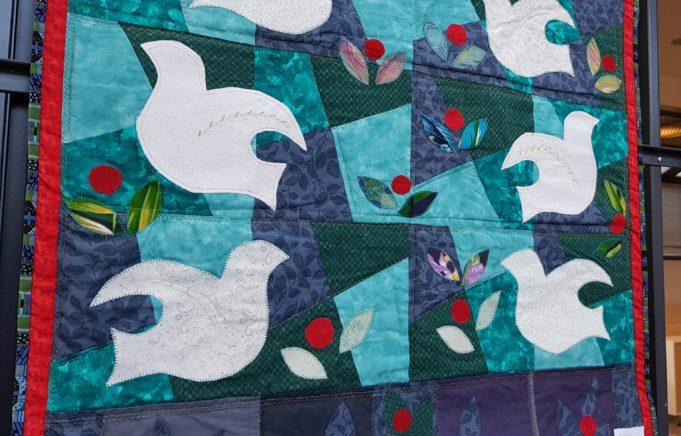 Tilkkutyö jossa valkoisia kyyhkyjä ja punaisia kukkia sinisellä pohjalla.